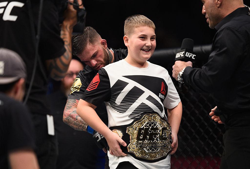 Promessa é dívida. Em gesto de lealdade, amizade e gratidão, Cody Garbrandt veste Maddux Maple com seu cinturão dos pesos galos do UFC, vencido no UFC 207 após derrotar Dominick Cruz. (Foto: Jeff Bottari/Zuffa LLC/Zuffa LLC via Getty Images)